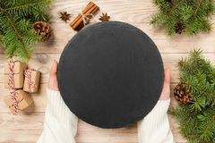 Famale hand hold Black slate round stone on wooden background with christmas decoration. top view, copy space. New Year concept stock image