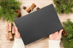Famale hand hold Black slate round stone on wooden background with christmas decoration. top view, copy space. New Year concept stock photos