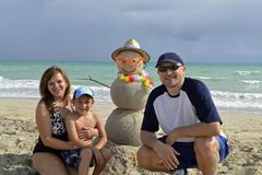 Family winter vacation. Portrait of the happy family at the beach on winter vacation with snowman made out of sand Royalty Free Stock Photos