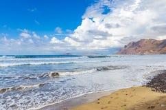 Famarastrand at low tide met de eilanden van archipel Chinijo op achtergrond stock afbeeldingen