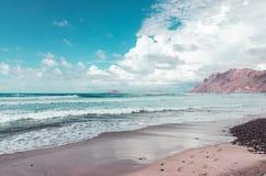 Famarastrand at low tide met de eilanden van archipel Chinijo op achtergrond royalty-vrije stock afbeelding