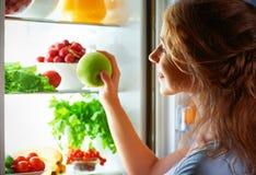 Fame di notte Donna nello scuro al frigorifero aperto fotografia stock libera da diritti