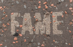 Fame written in white capital letters on a street pavement Royalty Free Stock Image