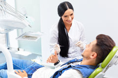 Famele dentist and man in dentists office.  Dentist and Patient Royalty Free Stock Photography