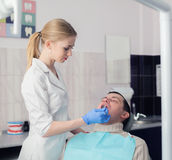Famele dentist and man in dentists office. Dentist and Patient Stock Images