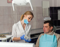 Famele dentist and man in dentists office. Dentist and Patient. Famele dentist and men in dentists office royalty free stock photos