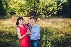 Famiglia abbastanza felice per una passeggiata nella caduta del parco Fotografia Stock