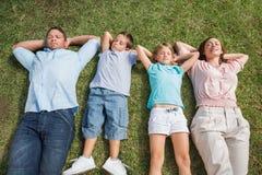 Famiglia addormentata che si trova sull'erba in una fila Immagine Stock