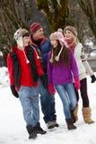 Famiglia adolescente che cammina lungo la via dello Snowy Fotografie Stock
