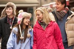 Famiglia adolescente che cammina lungo la via dello Snowy Immagini Stock