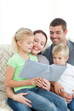 Famiglia adorabile che legge insieme un libro Fotografie Stock Libere da Diritti
