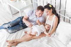 Famiglia adorabile che si siede insieme sul letto Immagine Stock Libera da Diritti