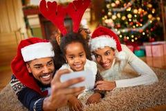 Famiglia adorabile di Natale che fa selfie Fotografia Stock