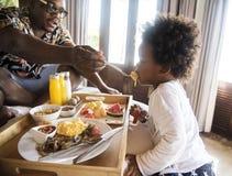 Famiglia africana che mangia prima colazione a letto fotografia stock