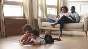Famiglia africana felice con i bambini nelle attività di svago del salone stock footage