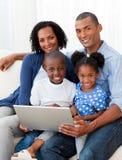 Famiglia Afro-American che per mezzo di un computer portatile sul sofà Immagine Stock