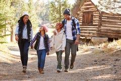 Famiglia afroamericana che cammina attraverso il terreno boscoso di caduta Fotografia Stock Libera da Diritti