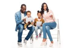 famiglia afroamericana felice che si siede insieme e che per mezzo dei dispositivi digitali fotografia stock libera da diritti