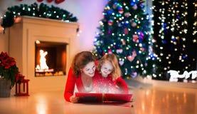 Famiglia al camino sulla notte di Natale Immagine Stock