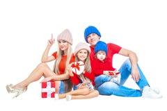 Famiglia al Natale Famiglia allegra in cappelli che esaminano macchina fotografica e che sorridono mentre isolato su bianco Conte fotografia stock