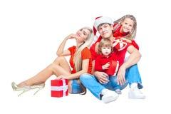 Famiglia al Natale Famiglia allegra in cappelli di Santa che esaminano macchina fotografica e che sorridono mentre isolato su bia immagini stock libere da diritti