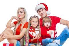Famiglia al Natale Famiglia allegra in cappelli di Santa che esaminano macchina fotografica e che sorridono mentre isolato su bia immagine stock