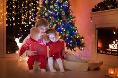 Famiglia al posto del fuoco sul Natale Fotografia Stock