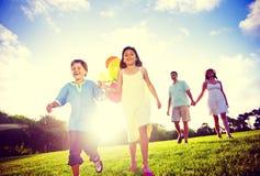 Famiglia all'aperto che cammina verso il concetto di svago della macchina fotografica Fotografia Stock