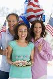 Famiglia all'aperto sul quarto di luglio con le bandierine Fotografia Stock