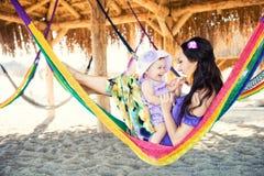 Famiglia alla moda felice con la figlia sveglia che si rilassa in amaca sulle vacanze estive alla luce del sole di sera sulla spi Immagine Stock
