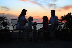 Famiglia alla tabella sulla spiaggia sul tramonto Fotografia Stock