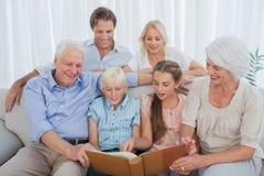 Famiglia allargata che esamina una foto dell'album fotografia stock