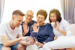 Famiglia allargata che fa una video chiamata e che ondeggia al visitatore Multi famiglia asiatica della generazione con le coppie fotografia stock