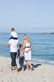 Famiglia allegra che cammina sulla sabbia fotografia stock libera da diritti