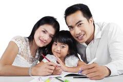 Famiglia allegra che fa insieme compito scolastico Immagine Stock