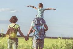 Famiglia allegra che fa un'escursione sul prato Fotografia Stock