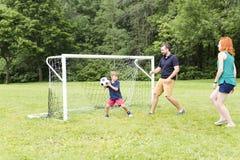 Famiglia allegra che gioca a calcio in un parco fotografia stock libera da diritti