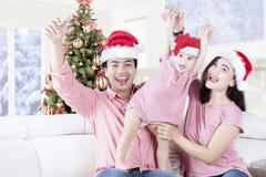 Famiglia allegra che porta il cappello di Santa a casa Fotografia Stock Libera da Diritti