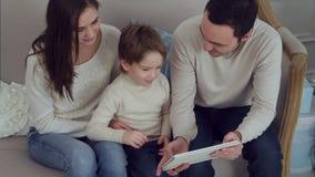 Famiglia allegra che si siede nel salone divertendosi con la compressa digitale che Santa Claus ha portato loro stock footage