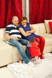 Famiglia allegra con il bambino in salone Fotografia Stock Libera da Diritti