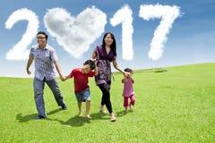 Famiglia allegra con la nuvola 2017 sul prato Fotografia Stock Libera da Diritti