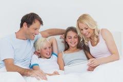 Famiglia allegra facendo uso della compressa digitale Immagine Stock