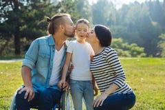Famiglia amabile che bacia figlia sulle guance Fotografia Stock Libera da Diritti
