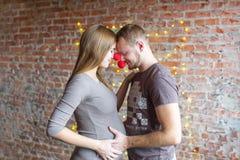 Famiglia amorosa delle coppie che abbraccia con la pancia incinta fotografia stock libera da diritti