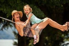 Famiglia amorosa felice! Giovane madre e sua la figlia del bambino che oscillano sulle oscillazioni e che ridono una sera di esta immagini stock
