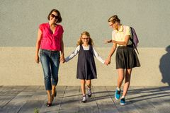 Famiglia amorosa felice - scolara della figlia e della madre, tenentesi per mano Di nuovo al banco immagine stock