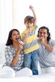 Famiglia Animated che canta con i microfoni Fotografia Stock