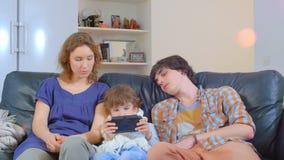 Famiglia annoiata che si siede sul sofà archivi video