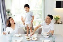 Famiglia asiatica che guarda il loro bambino poichè è risoluto e fiero infine stare sul tavolo da pranzo immagine stock libera da diritti