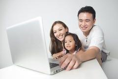 Famiglia asiatica che per mezzo del computer portatile Immagine Stock